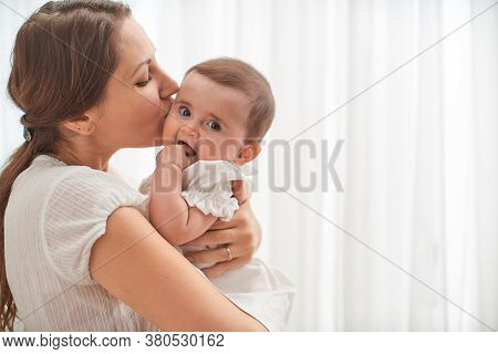 Loving Mother Embracing And Kissing Her Child On White. Mother And Her Baby Together. Happy Mother A