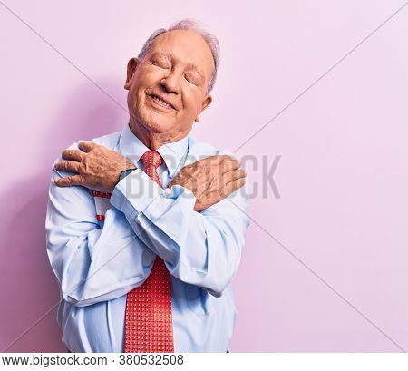Senior handsome grey-haired businessman wearing tie and shirt with name presentation sticker hugging oneself happy and positive, smiling confident. Self love and self care