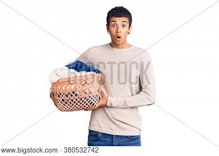 Young african amercian man holding laundry basket scared and amazed with open mouth for surprise, disbelief face