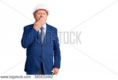 Senior handsome grey-haired man wearing suit and architect hardhat bored yawning tired covering mouth with hand. restless and sleepiness.