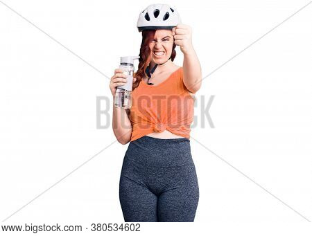 Young beautiful woman wearing bike helmet and holding water bottle annoyed and frustrated shouting with anger, yelling crazy with anger and hand raised