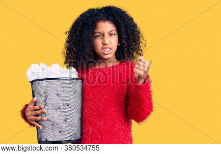 African american child with curly hair holding paper bin full of crumpled papers annoyed and frustrated shouting with anger, yelling crazy with anger and hand raised