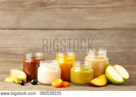 Glass Jars With Nutrient Baby Food And Fruit On Grey Background. Vegetable And Fruit Puree