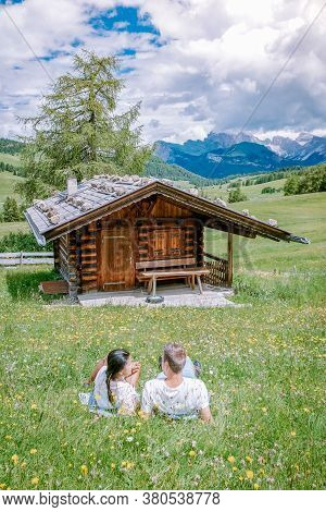 Couple Men And Woman On Vacation In The Dolomites Italy, Alpe Di Siusi - Seiser Alm With Sassolungo