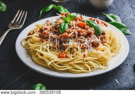 Spaghetti With Bolognese Sauce, Grated Parmesan Cheese And Fresh Basil Leaves