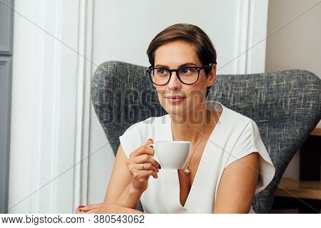 Portrait Of A Mid Adult Woman In Eyeglasses Sitting On An Armchair And Holding A Cup