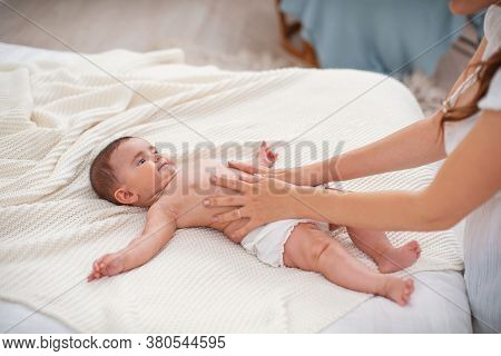 Baby Massage. Masseur Massaging Tummy Of Baby During Colic. Newborn Colicky Baby Without Clothes Lay