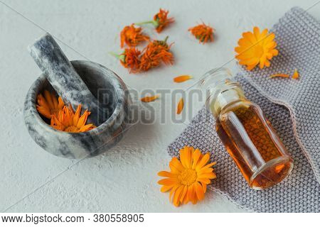 Natural Cosmetic Oil, Tincture Or Infusion And Mortar With Calendula Flowers Dry And Fresh On Light
