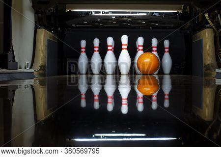 White Bowling Pins And An Orange Ball On A Bowling Alley. Beautiful Reflection. Close-up. Front View