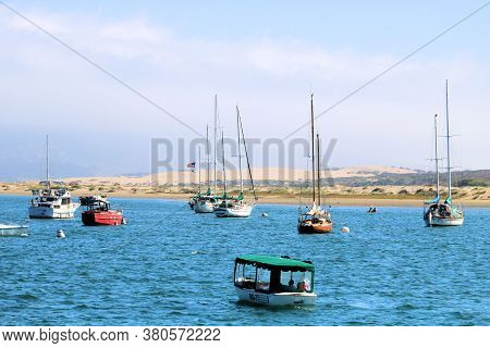 August 3, 2020 In Morro Bay, Ca:  Tour Boat Touring The Bay With Anchored Sail Boats Including Natur
