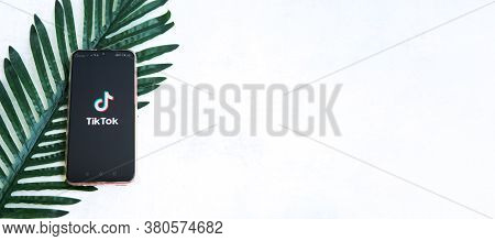 Tver, Russia-august 5, 2020, The Tik Tok Logo On The Smartphone Screen Against A Palm Leaf Backgroun