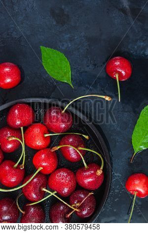 Cherry With Leaf On Plate And Water Dropsand On Black Stone Table. Ripe Ripe Cherries. Sweet Red Che