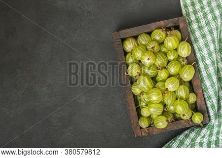 Ripe Green Gooseberry Berry In Wooden Box. Green Gooseberry On Black Background. Top View