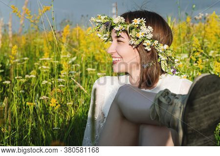 A Beautiful Woman In A White Dress In The Boho Style With A Wreath On Her Head Sitting In A Field In