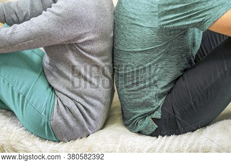 Couple With Their Backs Turned To Each Other Sitting On White Couch. Angry And Upset Couple Turning