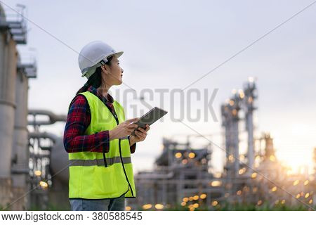 Asian Woman Petrochemical Engineer Working With Digital Tablet Inside Oil And Gas Refinery Plant Ind