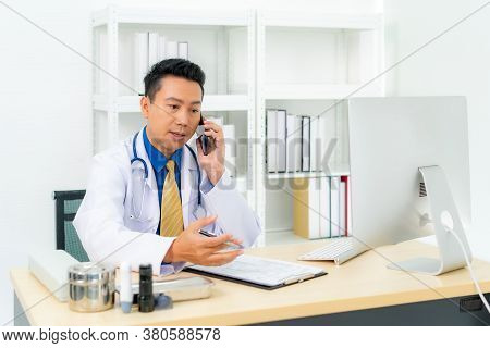 Asian Man Doctor Writing Document White Talking To Consulting Patient By Telephone Or Mobile Phone.