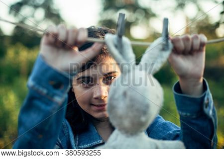 A teenage girl dries a toy hare on a clothesline.