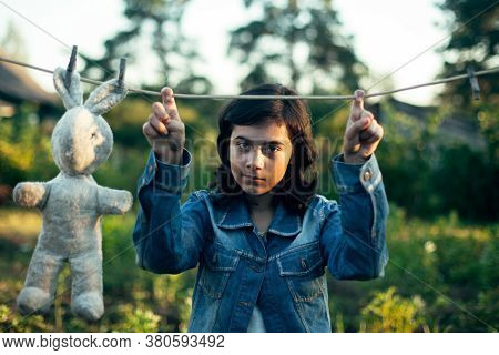 Teenage girl dries a toy hare on a clothesline.