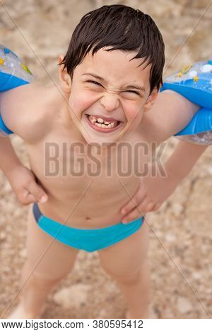 Child Wearing Inflatable Armbands Showing Off His New Teeth