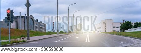Empty Asphalt Road With White Marking And Streetlight Against Bright Sunlight Under Blue Cloudy Sky