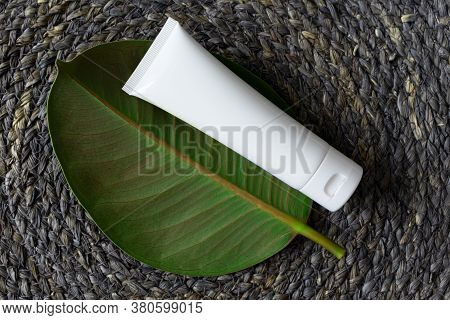 White Tube For Cream, Moisturizer, Lotion, Facial Cleanser Or Shampoo On Raffia Weave Background And