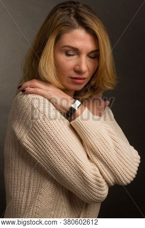 In Warm Toning, Portrait Of A Middle Aged Blonde Woman In White Clothes On A Light Gray Background.