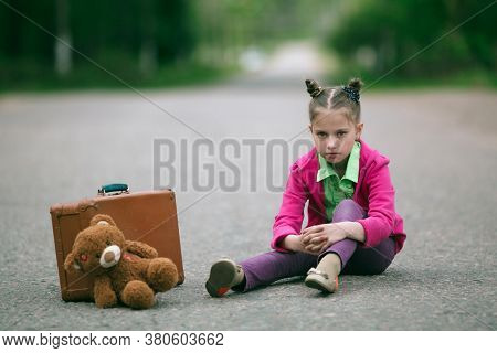 Little girl with a suitcase and a stuffed animal sitting on the road.