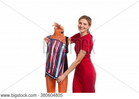 A Young Woman In A Red Dress Puts A Striped Dress On A Mannequin