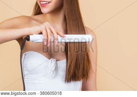 Smiling Woman Ironing Long Hair With Flat Iron. Happy Young Woman Straightening Hair With Straighten