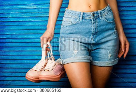 Girl With A Beautiful Figure In Jeans Shorts And Pink Shoes. Girl Hold A Pair Of Shoe. Woman Holding