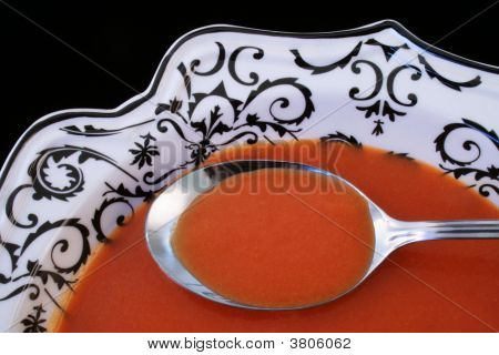 Closeup Of Tomato Soup On A Spoon With Black Background