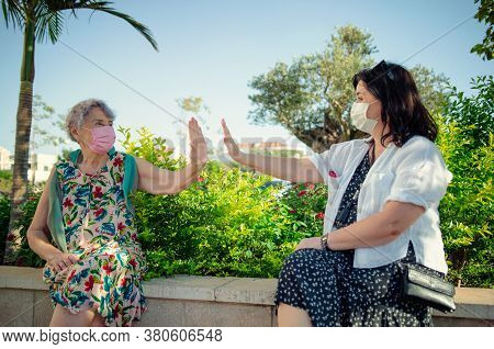 A High Air Five Gesture Between Caregiver And An Elderly Woman In Face Masks