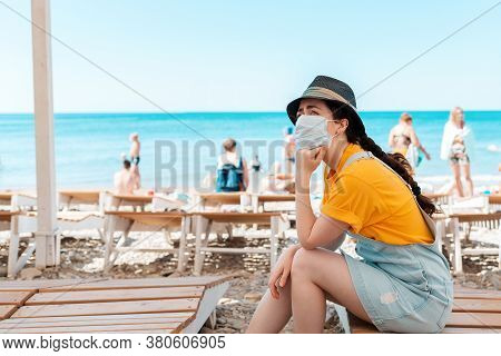 Portrait Of Woman In A Medical Mask Sits Bored On A Chaise Longue, Her Chin Propped On Her Hand. In
