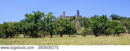 Ruines Of Hazmburk Castle On Top Of Mountain Peak Of Ceske Stredohori Range. Fruit Trees And Blue Sk