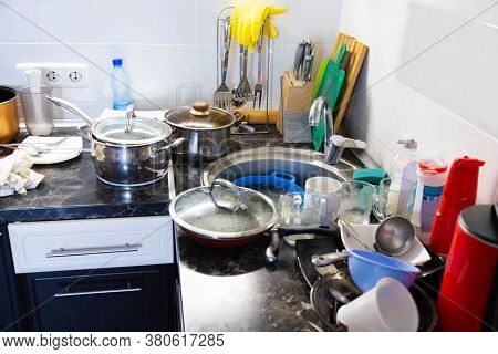 A Pile Of Dirty Dishes In The Metal Sink And On The Table Is Pouring. Kitchen After Breakfast, Lunch