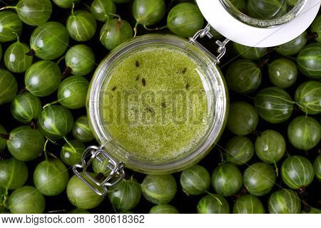 Gooseberry Jam In A Glass Jar And Berries Scattered Around. No-cook Jam. Food Background. Top View