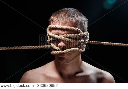 Portrait Of Binded Scary Man With Rope On Face