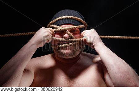 Picture Of Binded Fat Man In Cap With Rope On Face