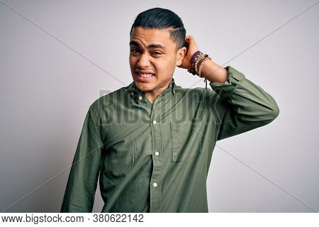 Young brazilian man wearing casual shirt standing over isolated white background confuse and wonder about question. Uncertain with doubt, thinking with hand on head. Pensive concept.