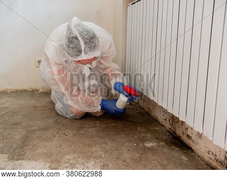 A Woman In A Protective Suit And A Respirator Sprays A Special Antifungal Spray On The Mold-infested