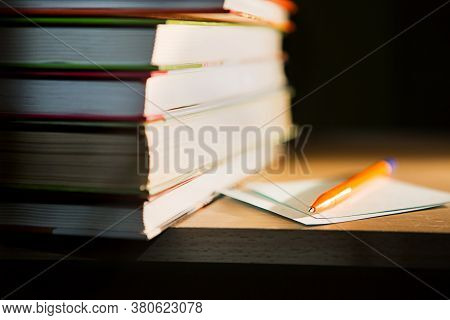 Close-up Of A Stack Of Books And A Pen With Paper For Notes. The Concept Of Home Reading Of Paper Bo