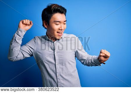 Young handsome chinese man wearing casual shirt standing over isolated blue background Dancing happy and cheerful, smiling moving casual and confident listening to music