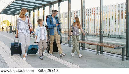 Caucasian Happy Family With Two Cute Small Kids Walking At Bus Stop Or Train Station, Carrying Suitc
