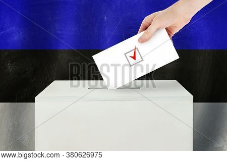 Estonian Vote Concept. Voter Hand Holding Ballot Paper For Election Vote On Polling Station
