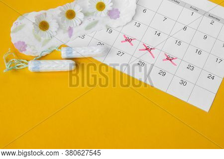 Menstrual Pads With Chamomiles On Menstruation Period Calendar On Yellow Background. The Concept Of