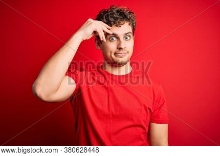 Young blond handsome man with curly hair wearing casual t-shirt over red background worried and stressed about a problem with hand on forehead, nervous and anxious for crisis