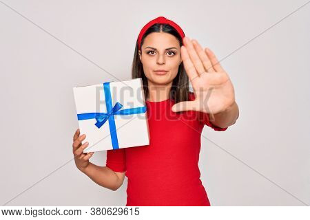 Young beautiful brunette woman holding birthday gift over isolated white background with open hand doing stop sign with serious and confident expression, defense gesture