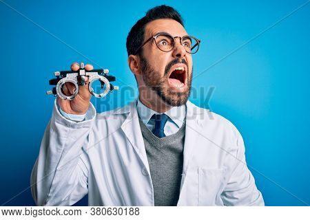 Young handsome optical man with beard holding optometry glasses over blue background angry and mad screaming frustrated and furious, shouting with anger. Rage and aggressive concept.