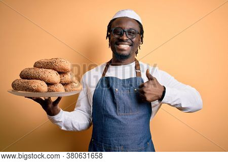 Young african american bakery man holding tray with healthy wholemeal bread happy with big smile doing ok sign, thumb up with fingers, excellent sign